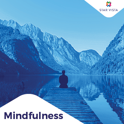 Person learning how to practice mindfulness on a blue peaceful background in the mountains with the StarVista logo.