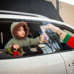 A child receives a holiday gift from a San Mateo County nonprofit from a holiday toy drive.