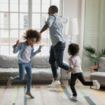 A father and his two children dance around in a photo for StarVista's Healthy Homes program featured by Popsugar.